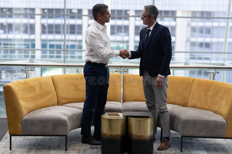 Caucasians business executives shaking hand in office. Front view of mature Caucasians business executives shaking hand standing in modern office stock images