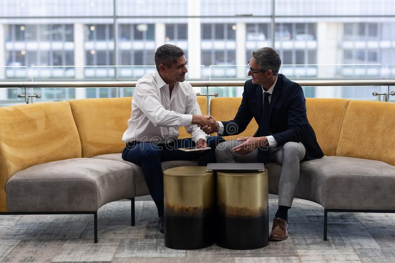 Caucasians of business executives shaking hand while sitting on the sofa. Front view of mature Caucasians business executives shaking hand while sitting on the royalty free stock photos