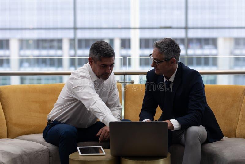 Caucasians dyrektory wykonawczy opowiada dyskutować nad laptopem podczas gdy siedzący na kanapie obraz stock