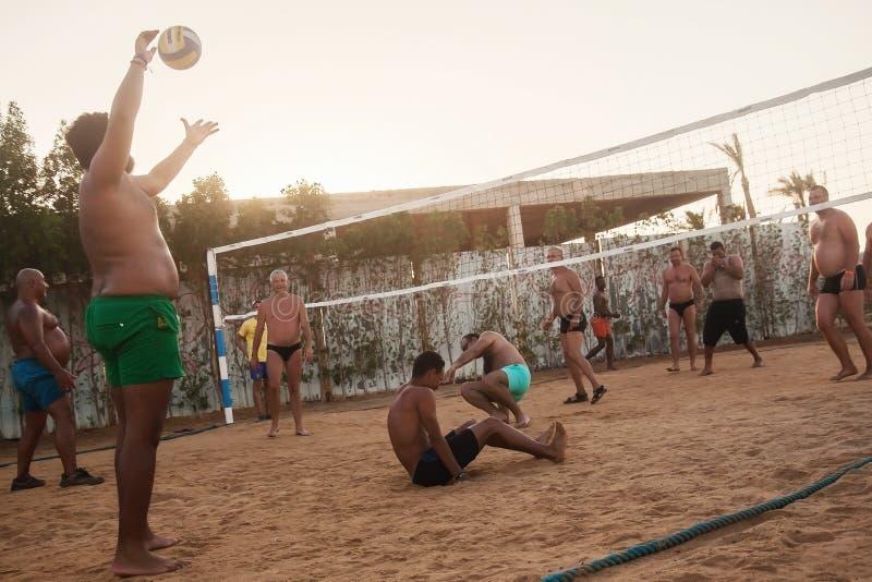 Caucasians masculinos, árabes, africanos que jogam o voleibol na praia fotos de stock