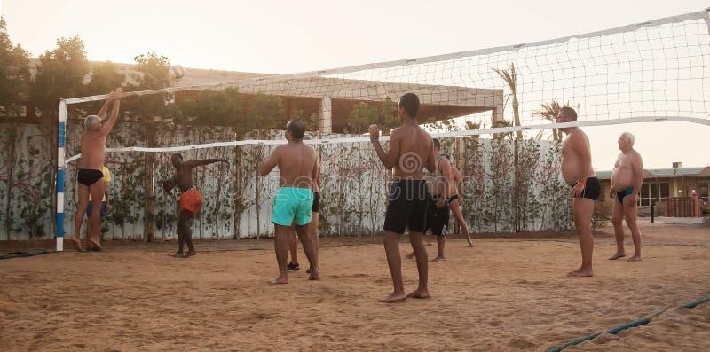 Caucasians masculinos, árabes, africanos que jogam o voleibol na praia foto de stock royalty free