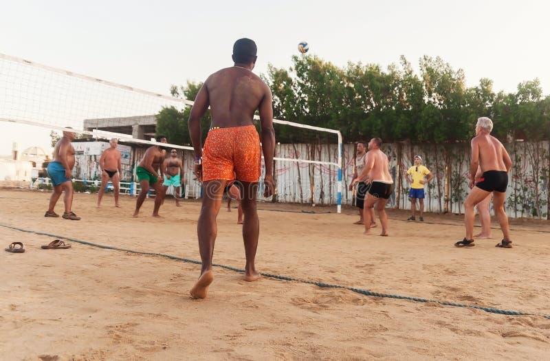 Caucasians masculinos, árabes, africanos que jogam o voleibol na praia no por do sol Egypt Hurghada O 5 de outubro dourado 7, 201 fotos de stock royalty free