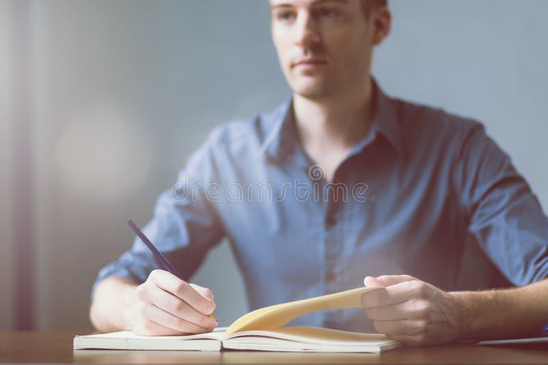 Caucasians novos do homem de negócios que sentam-se na tabela do escritório da mesa e que tomam notas no caderno Escrevendo e olh fotografia de stock