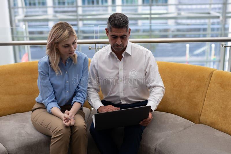 Caucasiansaffärsledare som använder bärbara datorn på soffan fotografering för bildbyråer