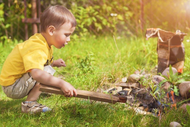 Caucasien Little Boy traitant le feu près de Firepace dehors image stock