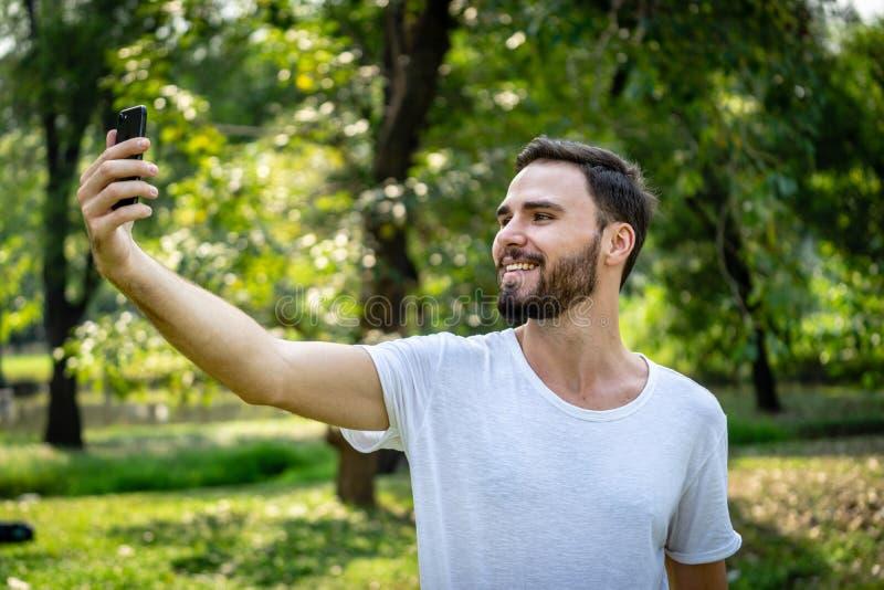 Caucasionmens selfie met zijn smartphone in openbaar park royalty-vrije stock afbeeldingen