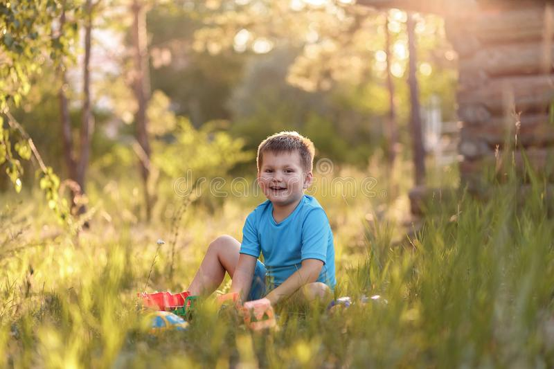 Caucasoid five-year-old boy in blue clothes sitting on the grass in the summer and playing with toys in the garden in the sunlight stock image