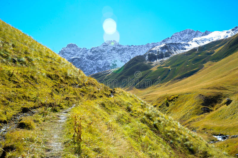 Caucasus mountains in summer, green hills, blue sky and snowy peak chiukhebi. royalty free stock photography