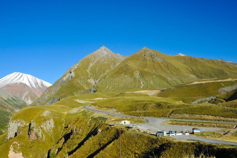 Caucasus mountains in summer, green hills, blue sky and snowy peak Mkinvari. road from Gudauri to Stepantsminda stock photo