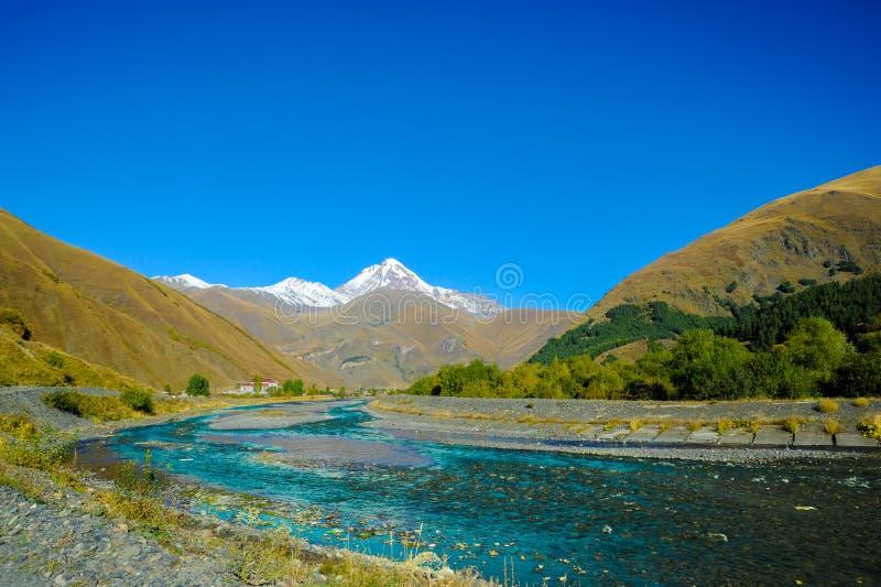 Caucasus mountains in summer, green hills, blue sky and snowy peak Mkinvari. road from Gudauri to Stepantsminda stock photos