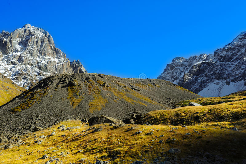 Caucasus Mountains, village Juta. green hill, blue sky, and snowy peak Chaukhebi in summer. royalty free stock images