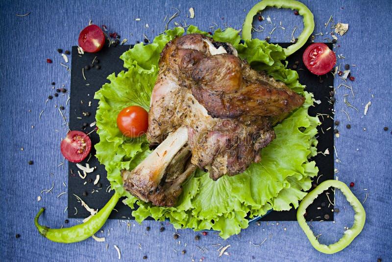 Cauda da carne de porco em uma grade com alface e tomates imagens de stock