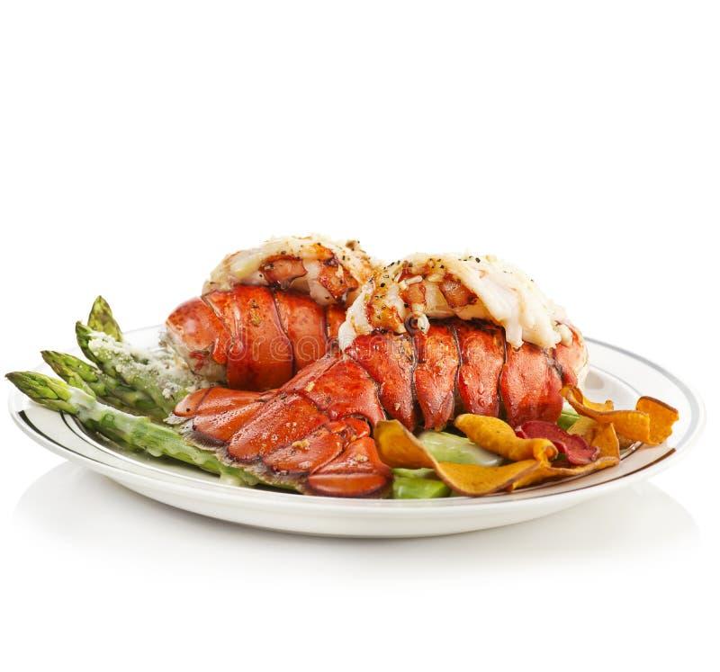 Caudas de lagosta grelhadas servidas com aspargo foto de stock