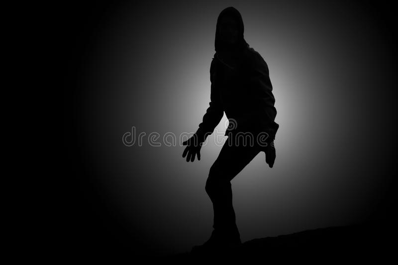 Caught in the act of crime. Silhouette spotlight of a hooded man looking suspicious and caught in the act of doing something illegal royalty free stock photography