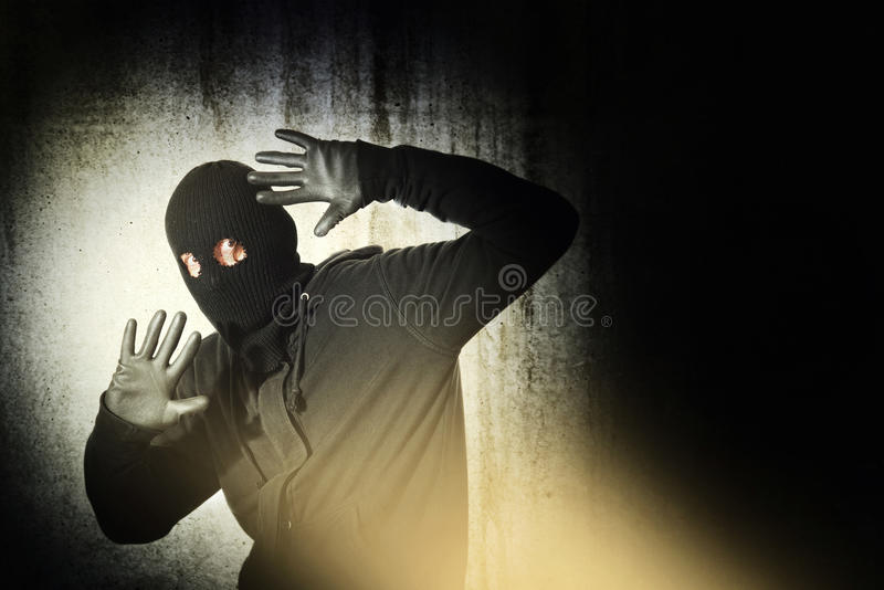 Caught burglar. Catch the burglar concept, thief with balaclava caught in front of the grunge concrete wall royalty free stock photo