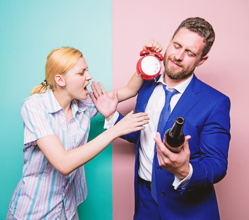 Caught for coming home late. Man suffering from alcoholism. Angry wife meeting drunk husband late at home. Businessman. With alcohol bottle and woman with clock stock image