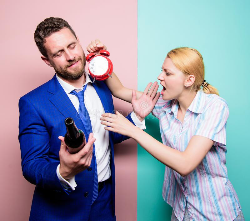 Caught for coming home late. Man suffering from alcoholism. Angry wife meeting drunk husband late at home. Businessman. With alcohol bottle and women with clock stock photo
