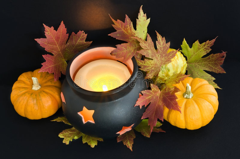 Cauldron and pumpkins. A candle in a cauldron with maple leaves and pumpkins. The reflected light from the flame casts an orange spooky glow on the background royalty free stock image