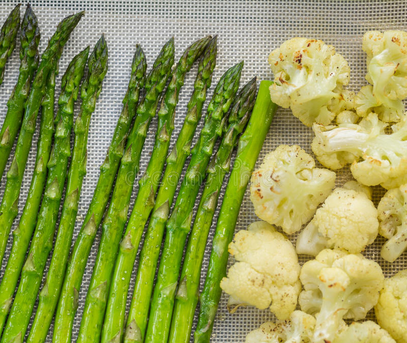 Cauliflower And Asparagus Being Roasted In Oven Royalty Free Stock Images