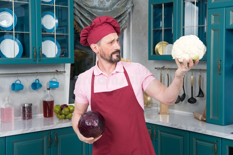 Cauliflower better red cabbage and chef agreed. Man shows big Cauliflower before steam cooking. Man holds vegetables in hands. Men chose cauliflower to cook royalty free stock photo