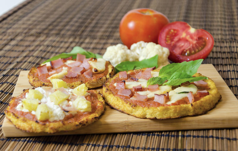 Cauliflower pizza. Three small round baked pizzas made of cauliflower crust and topped with bacon, ham, halloumi cheese, cottage cheese, lountza, pineapple stock images