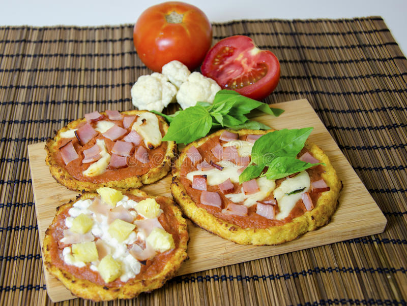 Cauliflower pizza. Three small round baked pizzas made of cauliflower crust and topped with bacon, ham, halloumi cheese, cottage cheese, lountza, pineapple royalty free stock photography