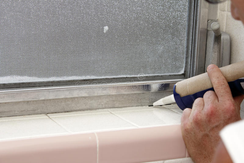 Caulking a Bathroom Window Frame royalty free stock image