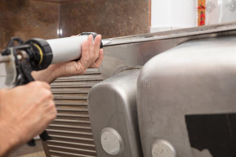Caulking an kitchen steal sink stock photos