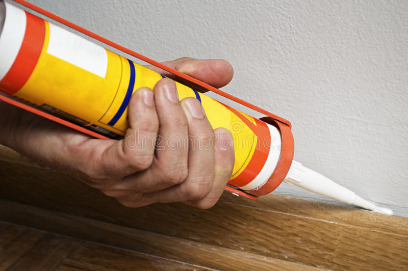 Caulking silicone on wooden batten. stock images