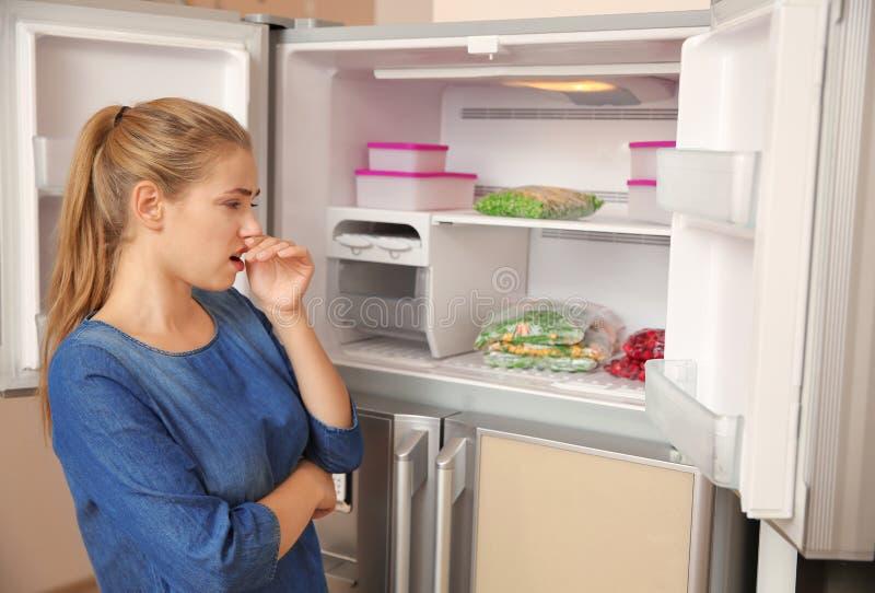 Causa de la nariz de la tenencia de la mujer joven del mún olor en refrigerador imágenes de archivo libres de regalías