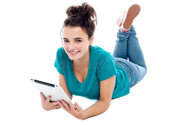 Causal tonåring som ligger på PCen för golvholdingtablet royaltyfria foton