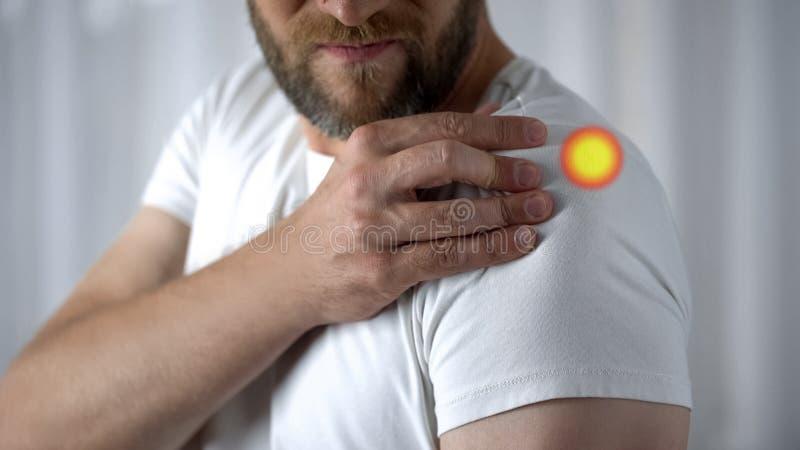 Cause dor no ombro indicado com o ponto, junção ferida homem após o exercício físico fotografia de stock