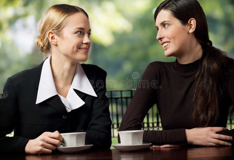 Causerie de sourire de deux jeune femmes d'affaires photos stock