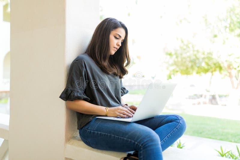 Causerie femelle avec des amis sur l'ordinateur portable pendant le temps libre images stock