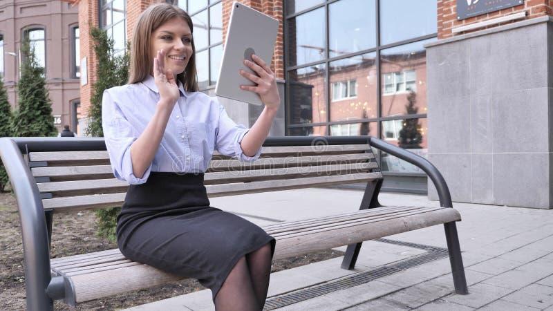 Causerie visuelle en ligne sur la Tablette par la femme s'asseyant en dehors du bureau image libre de droits