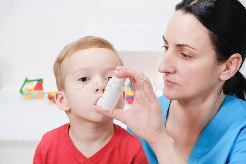 Causian little boy making inhalation with nebulizer at hospital. Child asthma inhaler inhalation nebulizer steam sick cough and medical concept royalty free stock photo