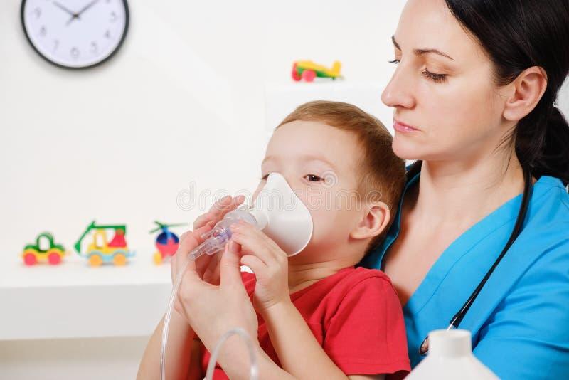 Causian little boy making inhalation with nebulizer at hospital. Child asthma inhaler inhalation nebulizer steam sick cough and medical concept stock image
