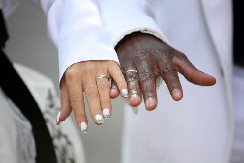 Causian und afro-amerikanische Paare, die Hand halten stockbilder