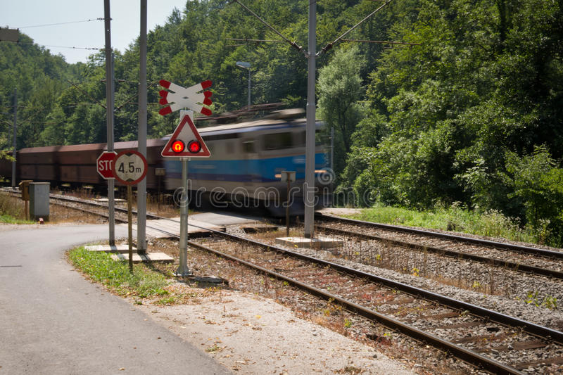 Caution going train. Motion blurred train passing a railroad crossing, Croatia royalty free stock photo