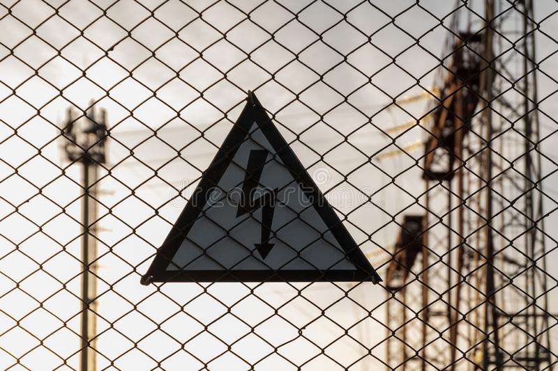 Caution high voltage. A triangular sign with a lightning bolt hanging on a lattice fence. The tower and high-voltage towers are. Blurred in the background royalty free stock photo