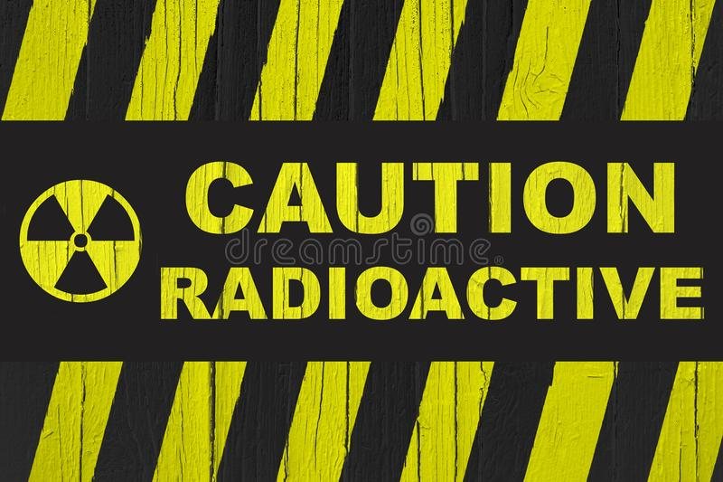 `Caution, radioactive` warning sign written in bold letters with radiation symbol and yellow and black stripes. Painted over cracked wood texture background royalty free stock photography
