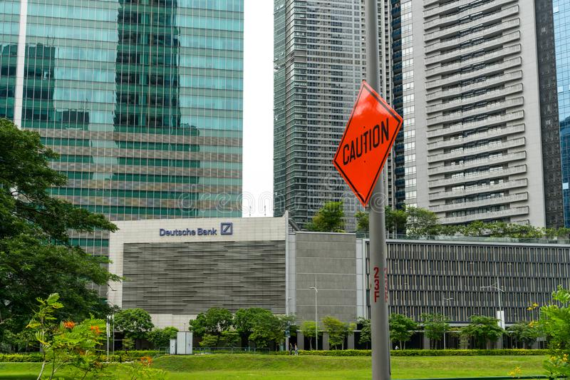 """Caution"" road sign next to Deutsche Bank logo stock photography"