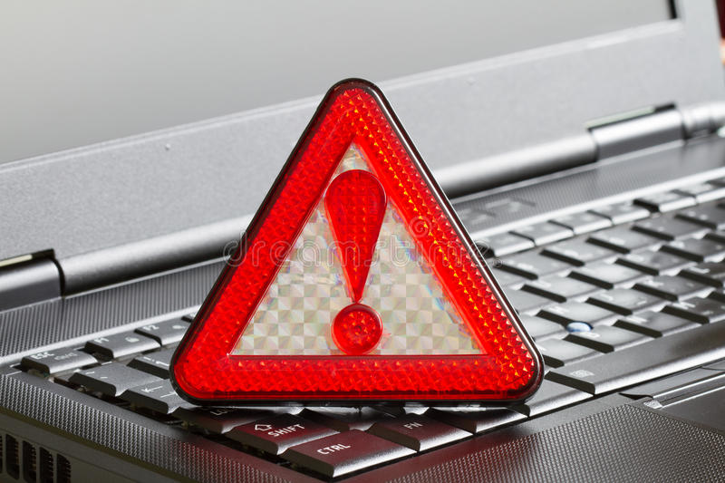Caution sign on black laptop computer virus detected alert hacking piracy royalty free stock image
