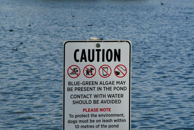 Caution sign for ` In the pond contact with water should be avoided, No swimming, No fishing, and Dogs must on leash. royalty free stock photo
