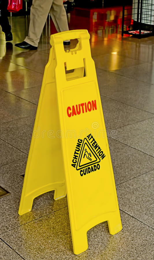 Caution sign on wet floor. Yellow tent-board Caution sign showing a person slipping on a wet floor after cleaning. Shiny tiles floor with a person walking past stock photography