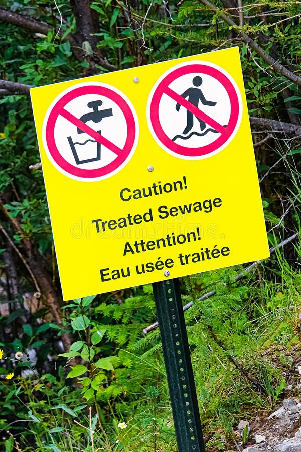 A caution treated sewage warning near running water royalty free stock photography