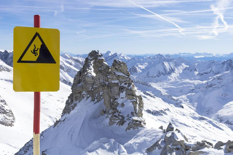 Caution warning sign in mountains ski resort - carefully down the cliff. Alpine Alps mountain landscape at Tirol, Top of. Caution warning sign in mountains ski royalty free stock photos