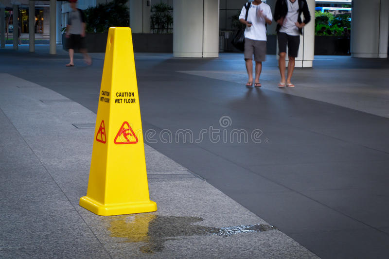 Caution wet floor. Safety cone standing beside spillage in the foreground and a couple of young men walking towards it in the background stock photo