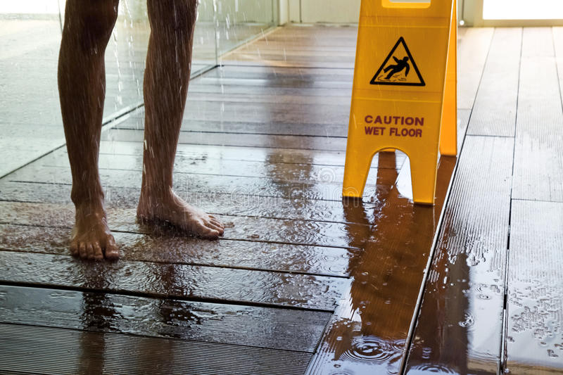 Caution wet floor sign next to man taking shower stock image