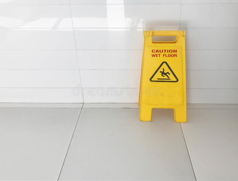 Caution yellow sign stated. `caution wet floor` during janitor cleanup service on ceramic tile floor royalty free stock images